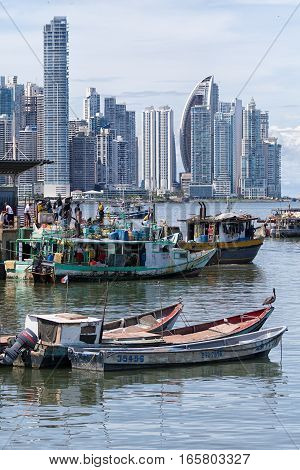 June 15 2016 Panama City Panama: small fishing boats floating on the water by the fish market with the modern downtown high-rise buildings in the background
