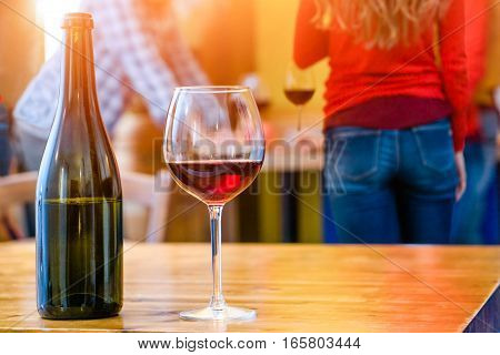 Friends drinking at home with red wine glass and bottle foreground on rustic table - Group of teenagers house party background with beverage close up as youth alcohol abuse concept