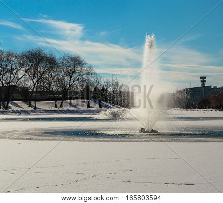 Frontal View Of A Water Fountain In A Frozen Pond