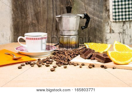 Rustic breakfast table with chocolate bar coffee beans mocha and sliced orange - View of vintage style kitchen with natural energy giving food on old wooden background - Concept of retro still life