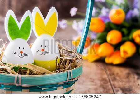 Easter rabbits in a basket and tulips on wooden table