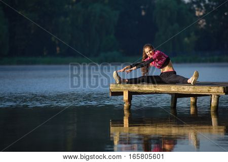 Woman Doing Exercises In Nature On The River