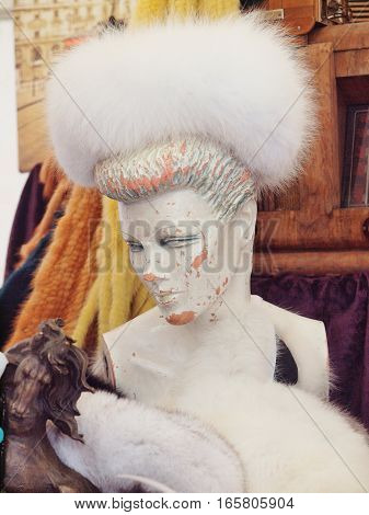 the old mannequin with white fur hat