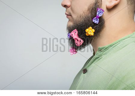 Man portrait n profile with hair clips on the beard over gray background