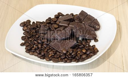 Chocolate with coffee beans on a white plate