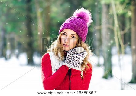 Outdoor close up portrait of young beautiful happy smiling girl walking on the street. Model closed her eyes and touching face wearing stylish knitted winter hat and gloves. Magic snowfall effect.