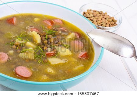 Hot and thick soup with lentils and sausages. Studio photo