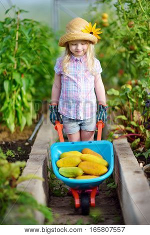 Adorable Little Girl Wearing Straw Hat Playing With Her Toy Garden Tools In A Greenhouse