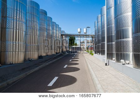 Modern metal tanks for maturing and cooling wine on the street along the road. Winery. Exterior.