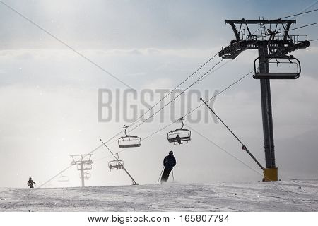 Skiers on ski chair lift in the fog. Strbske Pleso. High Tatra Mountains. Slovakia