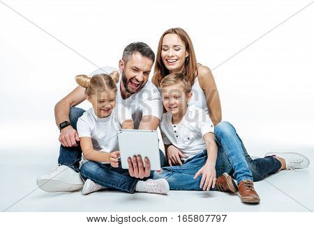 Smiling family in white t-shirts and jeans sitting together and using digital tablet