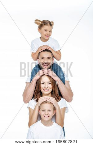 Happy family in white t-shirts having fun together and looking at camera isolated on white