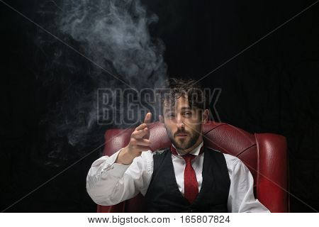 Businessman with smoking gun finger red. red chair on a black background