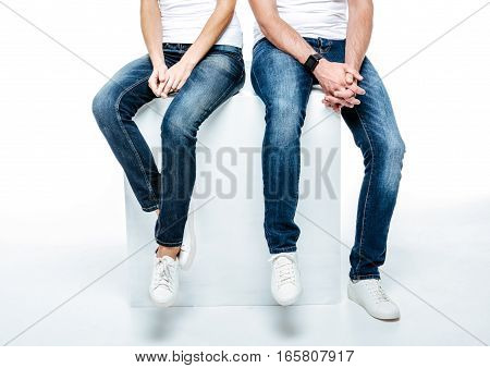 Low section of young couple sitting in jeans and white shoes on white