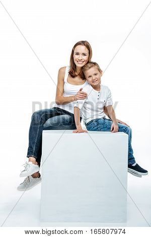 Smiling mother with son sitting together and looking at camera isolated on white