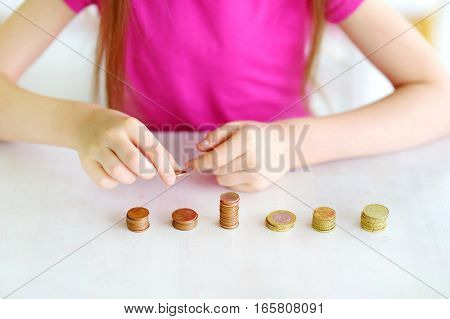 Child learning how to count money. Closeup of kid's hands and piles of coins. Money saving concept.