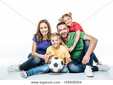Happy family in colored t-shirts sitting together with soccer ball on white