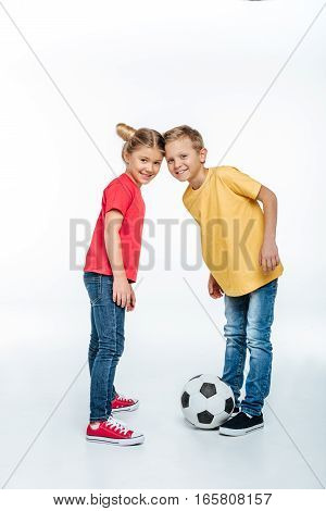 Full length view of Happy siblings in colored t-shirts standing with soccer ball and looking at camera on white
