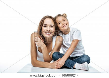 Smiling mother and daughter on white background