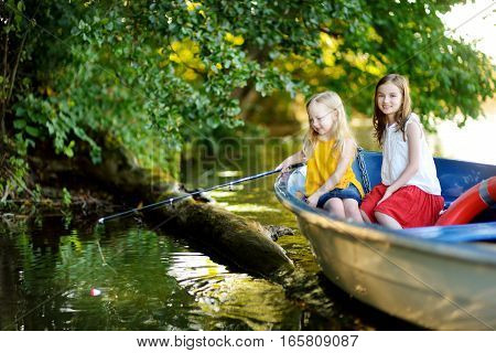 Two Cute Little Girls Having Fun In A Boat By A River At Beautiful Summer Evening