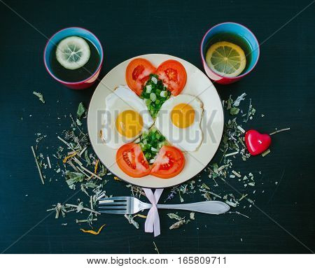 Scrambled eggs with tomatoes. Cup of tea