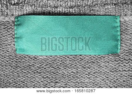 Blank cyan clothes label on gray knitted background