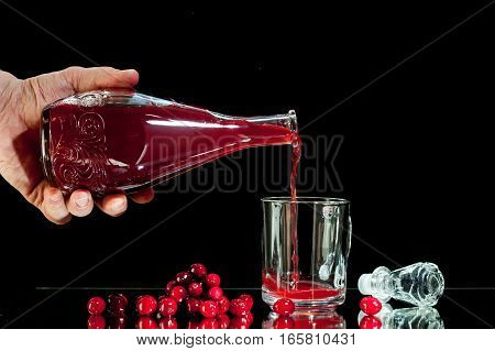 hand man pours red liqueur, cranberry juice, cranberry juice, isolated on a black background.