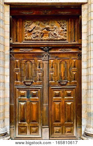 Wooden rectangle christian church door with a very detailed portrayal of a religious scene carved into the wood above the entrance itself. It is old / antique and beautifully ornate.