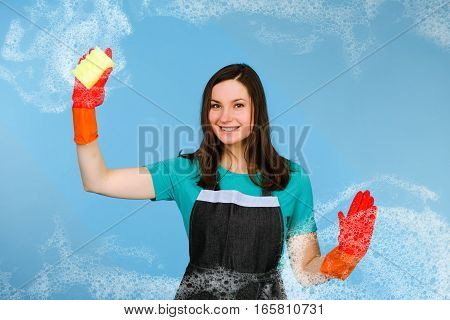 Positive woman cleaner in rubber gloves cleaning window with sponge and cleanser on blue background. Cleaning concept
