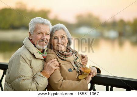 Happy senior couple  near river at autumn , blurred background