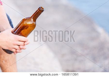 Man depressed holding wine bottle sitting on sea shore outdoor. People abuse and alcoholism problems