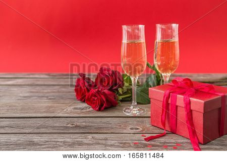 champagne glasses red gift box and red roses
