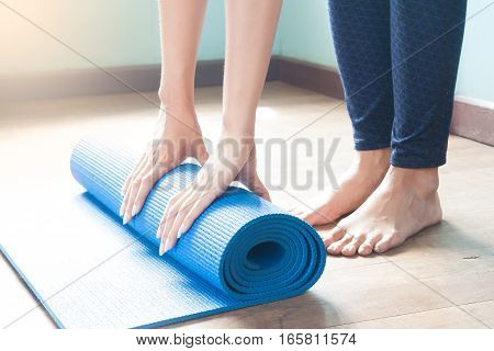 Young woman rolling yoga mat. Yoga at home