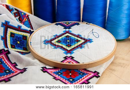 Traditional Slavic geometric pattern embroidered stitch cross on a white canvas with colored thread