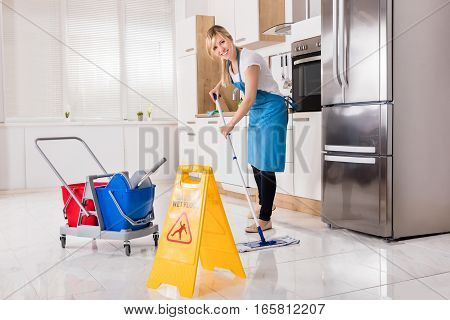 Cleaning Service Woman Using Mop To Clean Kitchen Floor