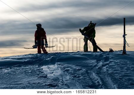 Silhouettes of two snowboarders on the mountain top before riding down in evening light