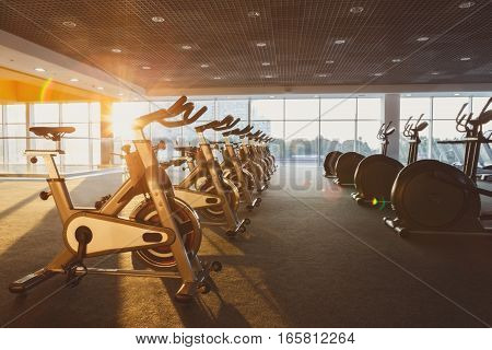 Modern gym interior with equipment. Fitness club with training exercise bikes, backlight in evening sunlight.