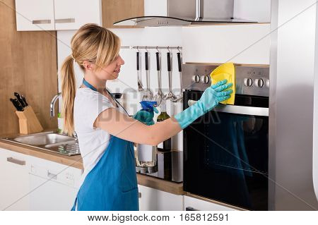 Young Housemaid Service Woman Cleaning Microwave Oven With Spray Bottle And Rag