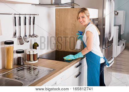 Young Smiling Housekeeping Service Woman Cleaning Dirty Induction Stove In Kitchen