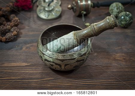 Singing Bowl against other religious ritual objects brown wooden table