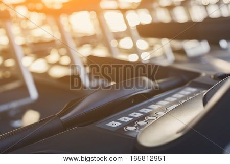 Modern gym interior equipment detail. Fitness treadmill's control panel for fitness cardio training in evening light. Healthy lifestyle concept