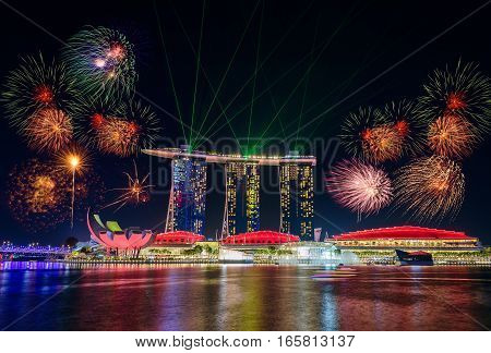 SINGAPORE - JULY 8, 2016 : Firework over Singapore Skyline and view of skyscrapers on Marina Bay at twilight time.