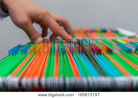 Abstract background of colorful hanging file folders in drawer. Mans hand Search document. Stock photo