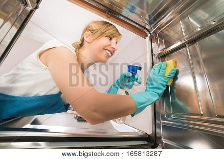 Young Happy Woman Cleaning Inside The Dishwasher With Rag And Spray Bottle In Kitchen