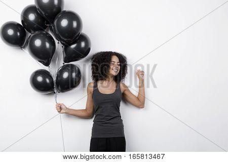 Happy woman holding many black balloons, indoors