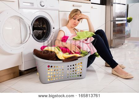 Exhausted Young Woman Sitting Near Washing Machine With Basket Full Of Clothes