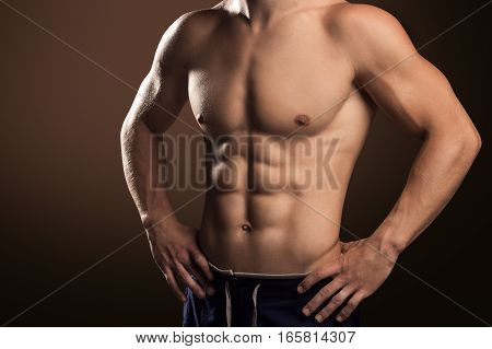 Muscular Handsome Man Demonstrates His Abdominal Muscles On Brown Background