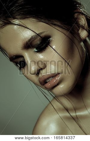 Portrait Of A Cute Fashion Woman With Wet Skin On Gray Background