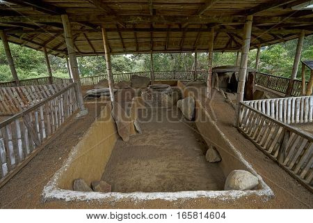 ancient pre-columbian tomb in San Agustin Colombia with statue in ALtos de los Idolos San Agustin Colombia