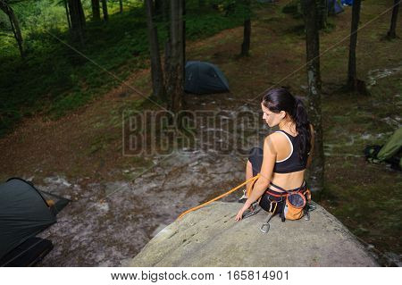 Female Climber Sitting On Big Natural Boulder In The Forest